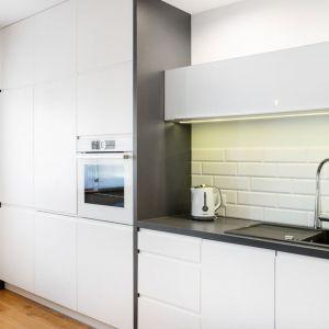 Prosta biała zabudowa kuchenna. Między szafkami znalazły się białe płytki-cegiełki. Projekt: Krystyna Dziewanowska, zdjęcia Mateusz Torbus/7TH IDEA