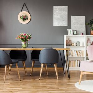 Ściany pomalowane głęboką barwą w intensywnym macie skomponują się z szarymi krzesłami oraz drewnianymi akcentami. Wystrój uzupełni designerski fotel w pudrowym różu, który dyskretnie ożywi wnętrze i doda mu przytulności. Fot. Tikkurila