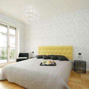 Ścianę za łóżkiem w sypialni wykończono jasną tapetą o subtelnym wzorze. Projekt: Justyna Smolec. Fot. Bartosz Jarosz