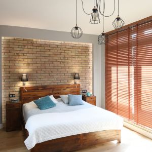 Ścianę za łóżkiem w sypialni wykończono cegłą, która doskonale pasuje do drewna. Projekt: Maciejka Peszyńska-Drews. Fot. Bartosz Jarosz