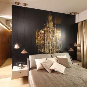 Ścianę za łóżkiem w sypialni wykończono tapetą o ciekawym wzorze. Projekt: Laura Sulzik. Fot. Bartosz Jarosz