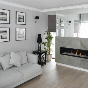 Salon powiększony optycznie dzięki jasnoszarej ścianie, jasnym meblom i lustrzanym powierzchniom. Projekt: Magdalena Smyk. Fot. Bartosz Jarosz