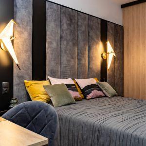 Ścianę za łóżkiem zdobi piękny, tapicerowany zagłówek w szarym kolorze. Elegancji dodają mu elementy w czarnym kolorze. Projekt: Donata Gadalska DG Studio. Fot. Jacek Fabiszewski