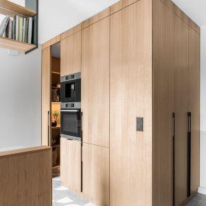 Pani domu lubi gotować, dlatego kuchnia musiała być i ładna, i funkcjonalna. Na zdjęciu wysoka drewniana zabudowa skrywająca sprzęt agd. Projekt: Marta i Michał Raca, pracownia Raca Architekci. Zdjęcia: Fotomohito