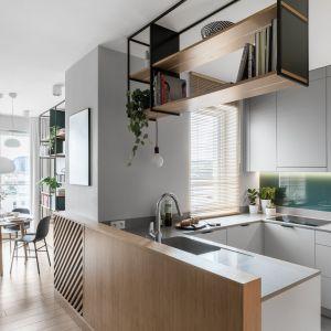 Kuchnia w kształcie litery C oddzielona od salonu dębową ścianką. Projekt: Marta i Michał Raca, pracownia Raca Architekci. Zdjęcia: Fotomohito