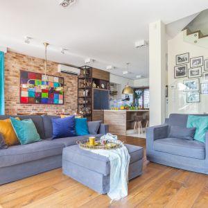 Sofa, fotel i puf organizują strefę wypoczynkową w salonie. Projekt Monika Pniewska. Fot. Pion Poziom