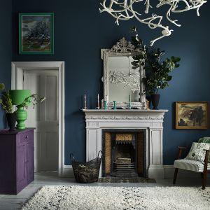 Ściana w salonie pomalowana farbą Wall Paint w kolorze Aubusson Blue, kominek i rama lustra wykończona farbą Chalk Paint™ w kolorze Paloma. Fot. Annie Sloan