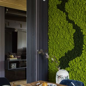 Soczysta zieleń pachnącego lasem chrobotka doskonale prezentuje się w połączeniu z prostym, drewnianym blatem znajdującego się nieopodal stołu, granatowymi krzesłami wykończonymi miękkim welurem i śnieżnobiałą, chińską porcelaną. Projekt Tissu Architecture. Fot. Yassen Hristov