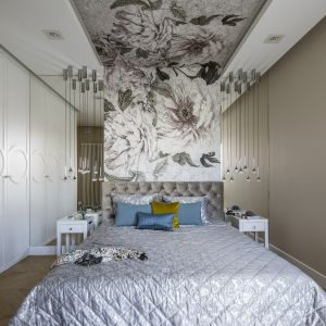 Zaaranżowana w wyciszającej palecie bieli, szarości i modnego toupe sypialnia, pozwala wybrzmieć prawdziwej bohaterce tego wnętrza, czyli florystycznej tapecie biegnącej przez ścianę oraz całą długość sufitu, i budującej oś pomieszczenia. Projekt Tissu Architecture. Fot. Yassen Hristov