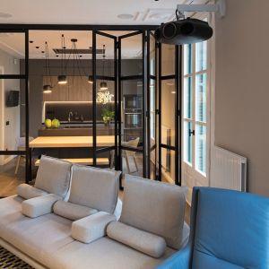 Salon od kuchni i jadalnia oddziela szklana ściana, którą w razie potrzeb można złożyć. Projekt: Gokostudio. Zdjęcia: Valentin Hincû