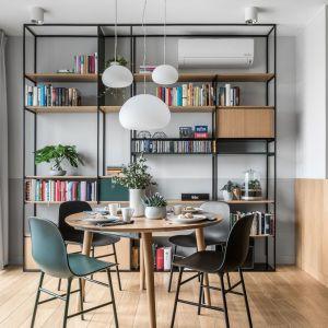W jadalni ustawiono okrągły stół i krzesła z marki Norman Copenhagen. Mamy tu też fajny regał w loftowym stylu. Projekt: Marta i Michał Raca, pracownia Raca Architekci. Fot. Fotomohito