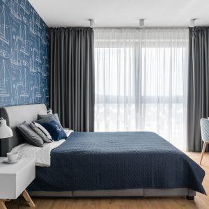 ścianę za wezgłowiem zdobi ciemnoniebieska tapeta. Projekt Studio Projekt. Fot. Fotomohito