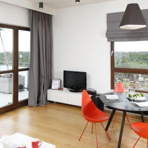 Połączenie salonu z małą jadalnią pozwoliło wyeksponować designerskie krzesła w czerwonym kolorze. To one nadają ton całej aranżacji. Projekt: Małgorzata Łyszczarz. Fot. Bartosz Jarosz