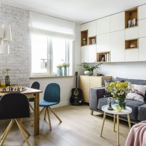 Prosty, drewniany stół i lekkie krzesła w niebieskim kolorze świetnie pasują do jasnego, nowoczesnego salonu. Projekt: Saje Architekci. Fot. fotomohito