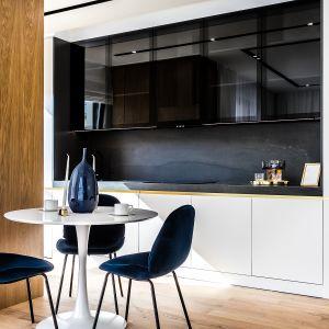 w stylowo urządzonym wnętrzu nie może zabraknąć ma stole w jadalni wazonu i szkła ozdobnego. Fot. Moovin Interiors