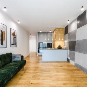 Świetnym pomysłem na aranżację ścian w stylowym salonie są modne obrazy i lustra. Fot. Moovin Interiors