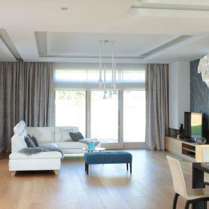 Białe lampy zwisające w sufitu stanowią fajną dekorację w salonie. Projekt: Agnieszka Hajdas-Obajtek. Fot. Bartosz Jarosz