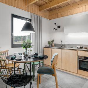 Niewielka kuchnia na jedną ścianę, tuż obok jadalnia - okrągły stół i wygodne krzesła. Projekt: Raca Architekci. Fot. Fotomohito