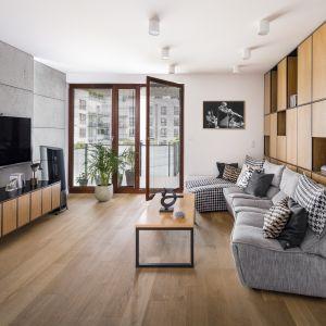 W nowoczesnym salonie z surowym betonem na ścianie dobrze wygląda podłoga w naturalnym drewnianym kolorze. Projekt: Zuzanna Kuc, ZU projektuje. Zdjęcia Łukasz Zandecki
