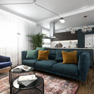 Kolorowa strefa wypoczynkowa w salonie - zielona sofa, kolorowe poduszki i niebieski fotel. Projekt: Marta Ogrodowczyk-Trepczyńska, Marta Piórkowska, Oktawia Rusin. Wizualizacje: Elżbieta Paćkowska