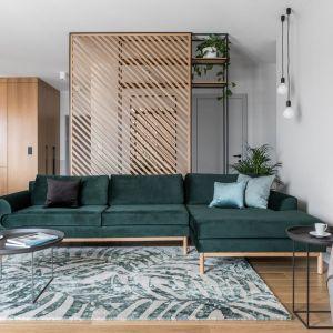 Ścianę za kanapę w salonie zdobią delikatne drewniane lamele oraz metalowy regał z miejsce na kwiaty. Projekt: Marta i Michał Raca, pracownia Raca Architekci. Fot. Fotomohito