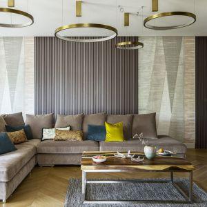 Ścianę za kanapą w salonie zdobi tapeta oraz grafitowe lamele, dzięki czemu wnętrze jest niezwykle eleganckie i stylowe. To połączenie prezentuje się idealnie. Projekt: Tissu Architecture. Fot. Yassen Hristov
