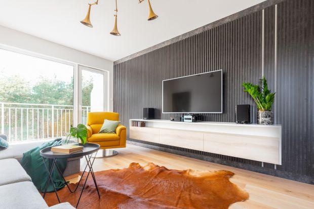 Jak wyeksponować ścianę z telewizorem? Z pomocą przyjdzie fornir eksponujący naturalny rysunek drewna, wzorzysta tapeta, czy efektowne panele dekoracyjne.