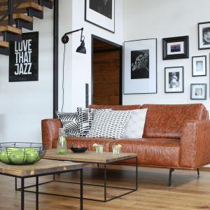 Ścianę za kanapą w salonie wykończony białą farbą, na tle które pięknie wyglądają zdjęcia w czarnym ramkach. Projekt: Katarzyna Walawska. Fot. Bartosz Jarosz