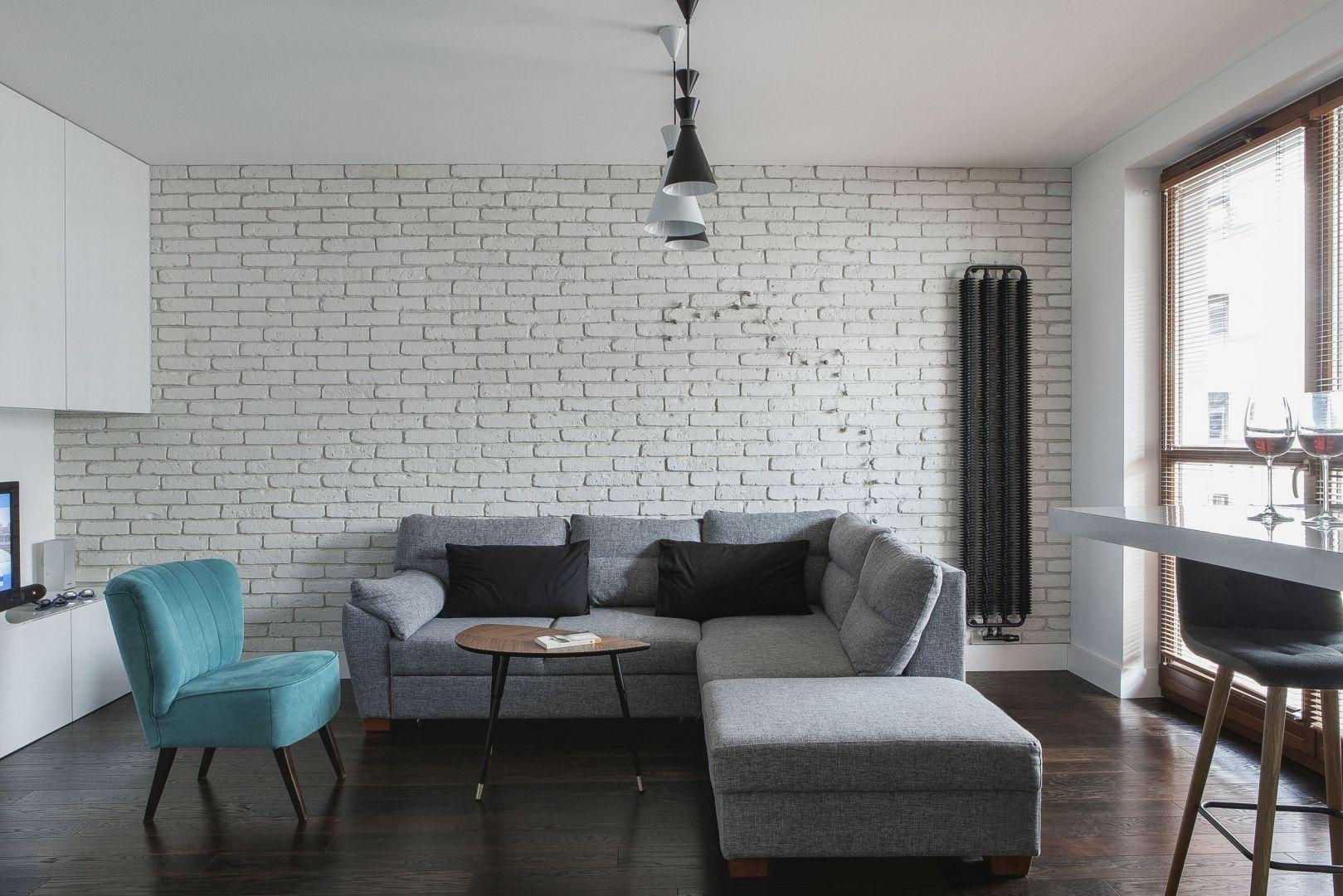 Ścianę za kanapą w całości wykończono cegłą w białym  kolorze, dzięki czemu salon jest jasny i nowoczesny. Projekt: MAFGroup. Fot. Emi Karpowicz