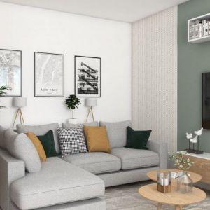 Fragment ściany za kanapą w salonie pomalowano jasnozieloną farbą, cześć obok - oklejono tapetą. To sposób na optyczne poprawienie jej niekorzystnych proporcji. Projekt i zdjęcia: Pracownia Architektoniczna MGN