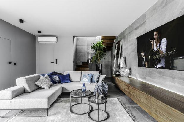 Szare ściany w salonie podkreślą jego nowoczesny wygląd. Sprawdzi się tu nie tylko farba, ale tez dekoracyjne tynki, płytki, a nawet beton.