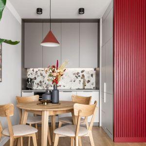 W małej kuchni kolor szary pięknie ożywia czerwień i dopełnia drewno. Projekt: Maria Nielubszyc, pracownia PURA design. Zdjęcia: Jakub Nanowski