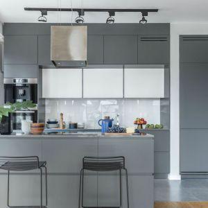 Białe szafki i ściana nad blatem fajnie wyróżniają sią na tle ciemniejszych szarości zastosowanych w kuchni. Projekt: Decoroom. Fot. Pion Poziom