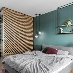 Ściana za łóżkiem w sypialni pomalowana farbą w modnym zielonym odcieniu. Półka w loftowym stylu pełni też funkcję kwietnika. Projekt: Marta i Michał Raca, pracownia Raca Architekci. Zdjęcia Fotomohito