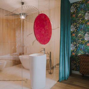 To duże pomieszczenie, w którym wolnostojąca wanna i umywalka już same w sobie tworzą oryginalną kompozycję.