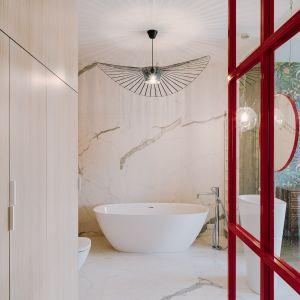"""W łazience znalazły się jednak również malinowe elementy, które przełamują całość – odejmują mu powagi, dodają pomieszczeniu pewnego """"twistu""""."""