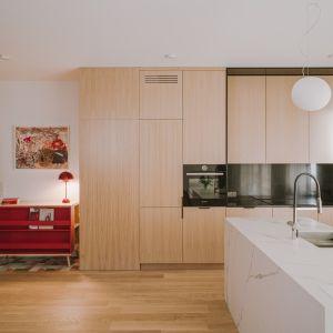Kuchenna zabudowa została sprytnie wkomponowana w to wnętrze, ponieważ szafki pasują kolorystycznie do regału, stolika kawowego, nóżek od krzeseł, a nawet do dębowej podłogi.
