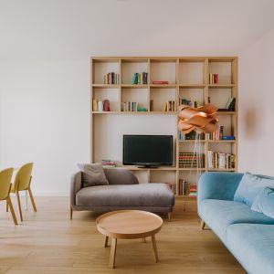 Strefa dzienna idealnie sprawdzi się podczas przyjmowania gości: mają do dyspozycji niebieską kanapę oraz szary szezlong.