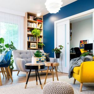 Mała szara sofa w salonie w towarzystwie żółtego wygodnego fotela. Projekt: wnętrza Krystyna Dziewanowska, Red Cube Design. Zdjęcia: Mateusz Torbus 7TH Idea