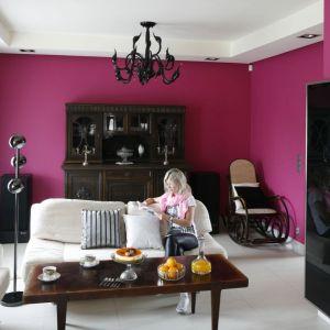 Wszystkie ściany w salonie pomalowano na bardzo mocny różowy kolor, z którym połączono ciemne meble oraz jasną podłogę i zestaw wypoczynkowy. To ciekawe, ale i odważne rozwiązanie. Projekt: Beata Ignasiak. Fot. Bartosz Jarosz