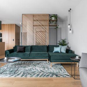 Zielona sofa pięknie prezentuje się na tle drewnianych elementów aranżacji. Projekt Raca Architekci. Fot. Fotomohito