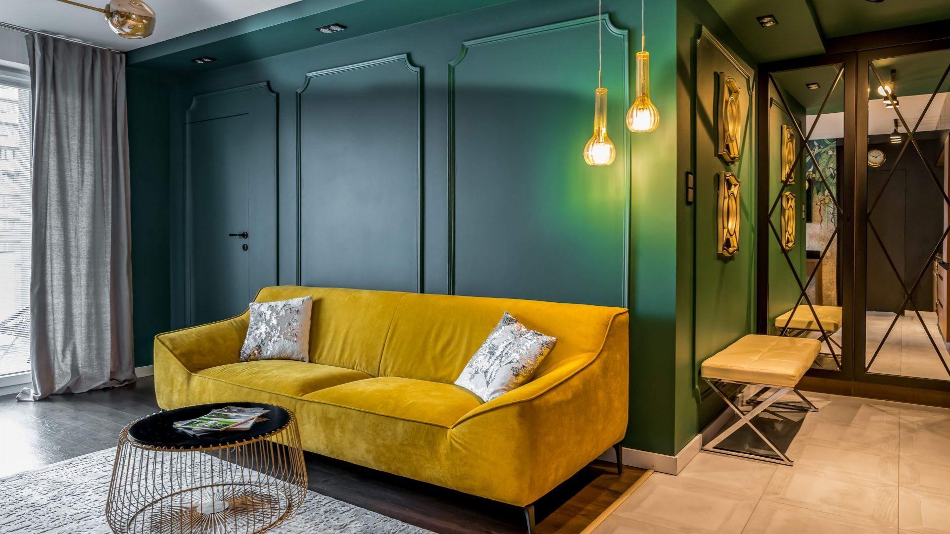 Ścianę za kanapą piękne zdobi sztukateria w zielonym kolorze, która nadaje wnętrzu elegancji. Projekt: Donata Gadalska. Fot. Jacek Fabiszewski