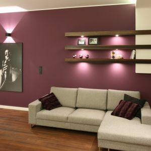 Pomalowana na fioletowy kolor ściana jest mocnym punktem nowoczesnego salonu. Projekt: Katarzyna Mikulska-Sękalska. Fot. Bartosz Jarosz.