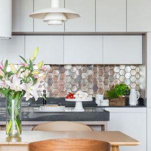 Ściana między kuchennymi szafkami pokryta błyszczącą mozaiką. Projekt: Dominika Wojciechowska, Nidus Interiors. Fot. Pion Poziom