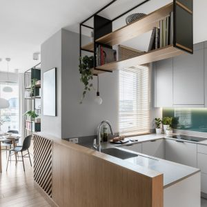 Ściana między kuchennymi szafkami wykończona szkłem laminowanym. Projekt: Marta i Michał Raca, pracownia Raca Architekci. Zdjęcia Fotomohito
