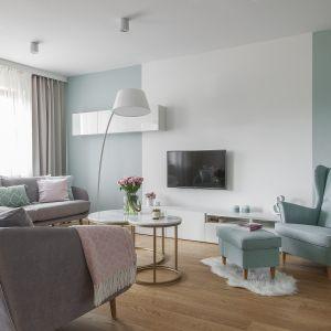 Pastelowy fotel idealnie komponuje się z szarą sofą. Projekt MAFgroup