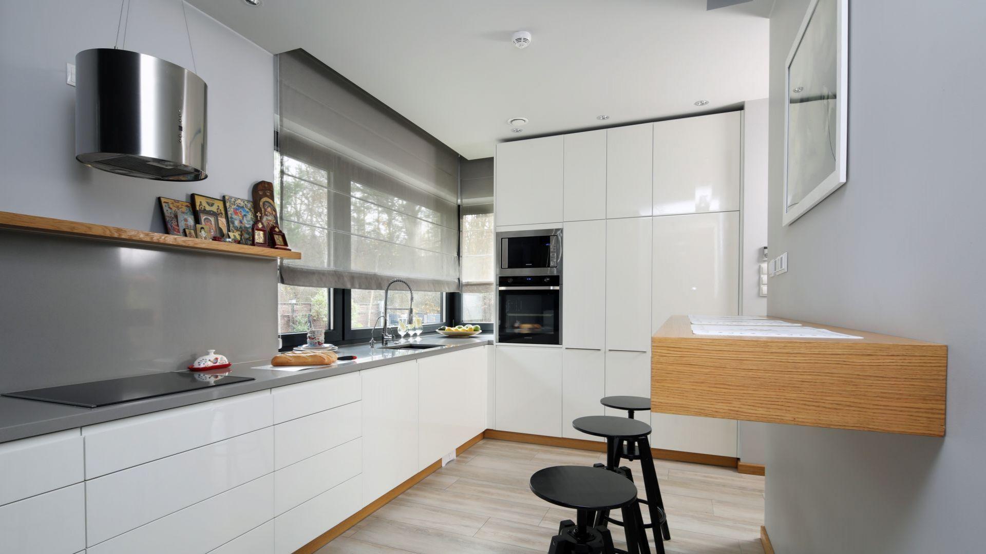 Szare ściany doskonale łączą się białą zabudowa meblową i drewnem. Projekt: Laura Sulzik. Fot. Bartosz Jarosz
