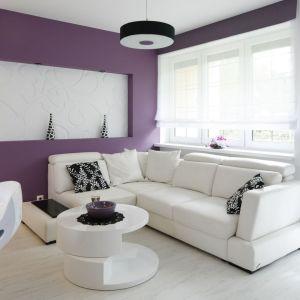 Białe ściany w salonie pięknie ożywia kolor fioletowy. Projekt: Joanna Ochota. Fot. Bartosz Jarosz