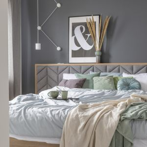 W sypialni pierwsze skrzypce gra drewniane łóżko z szerokim, tapicerowanym we wzór jodełki zagłówkiem. Projekt Zu Projektuje. Fot. Pion Poziom