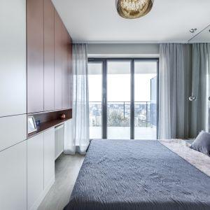 W sypialni białe fronty zabudowy meblowej ocieplono miedzianym odcieniem. Projekt: Justyna Mojżyk, poliFORMA. Fot. Monika Filipiuk-Obałek
